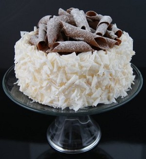 Fake Food Coconut Cake With Chocolate Swirls Top On Glass Pedestal