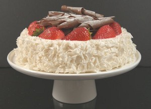 Fake Food Coconut Cake With Strawberries & Chocolate Swirls on Cake Pedestal